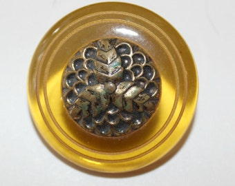 Vintage celluloid button with brass center design of leaves