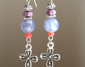 Beautiful handmade earrings, accented with gray faceted agate bead, purple glass bead silver tone cross, and a pop of orange.