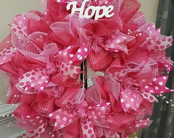 Breast cancer awareness 'Hope' wreath made of poly burlap and deco mesh in shades of pink, w/pink ribbon and pearl accents.