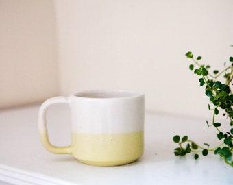 white and yellow stoneware ceramic coffee mug
