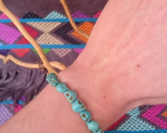 Tiny skull bracelet made of composite turquoise.