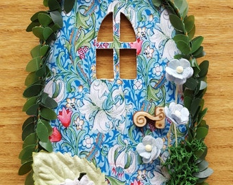 Fairy door with flowers, cat, leaves and moss