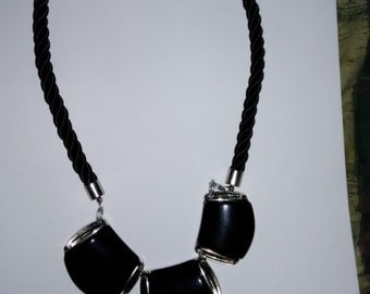 Black statement necklace on black rope
