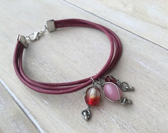 Pink leather bracelet with three strands and a variety of pink glass bead charms.
