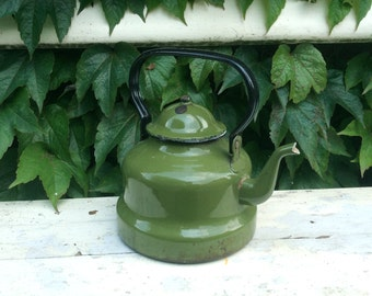 Large vintage dark green enamelware water kettle with black handle in country style or farmhouse style