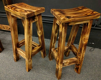 two fire scorched rustic bar stools with saddle seat