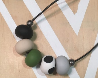 Polymer clay bead necklace. Spots black white green