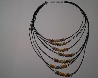 Necklace made of black leather cord strands and multi-metalic colored stardust beads