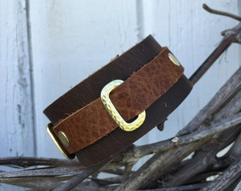 Genuine leather cuff with gold hardware.