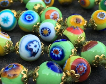 Necklace of Venetian millefiore beads in fresh green with multi colored murrine. Hand knotted with gold tone findings and clasp