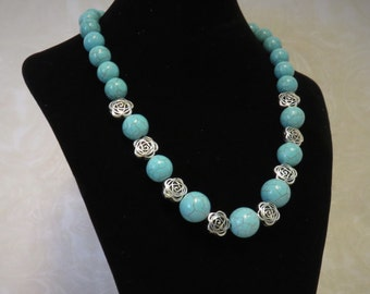 Turquoise Chunky Necklace w/ Silver Filigree Flowers In Front.