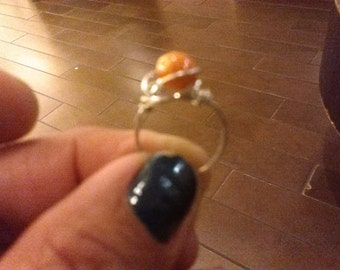 Cute little ring with yellow pearlish bead .