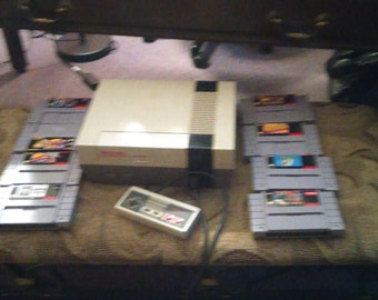 nintendo nes with 1 controller and 8 games