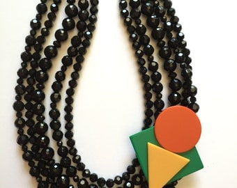 Multi-strand 1980's inspired necklace with black resin beads and detachable brooch.