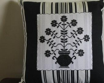 Black and white throw pillow with vase of flowers