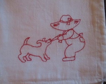 Little boy playing tug of war with his puppy tea towel