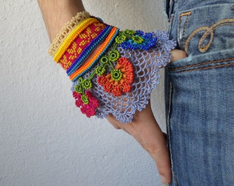 colorful asymmetric bracelet with magenta pink - yellow embroidered base, pink, persimmon and teal blue beaded flowers and blue crochet lace