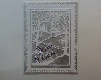 Christmas card with church,trees, birds and fence in silver and white.