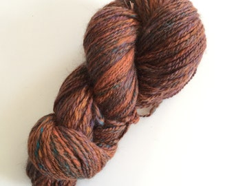 Handspun wool yarn multi colored approximately 216 yards. Browns,rust,blue 2 ply.