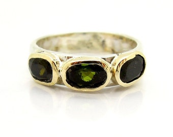 Green tourmaline ring set gold on top of a silver band