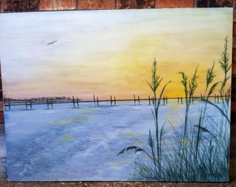 Original painting of warm sunset over calm blue water with pier along horizon and green grasses in foreground with seagull soaring in sky