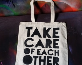 Take Care of Each Other tote bag stencil and spray paint street art by Rainbow Alternative