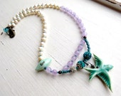 Diving to the lilacs - handmade bohemian asymmetric swallow necklace in turquoise, pearl and lilac - Songbead Uk, narrative art jewelry