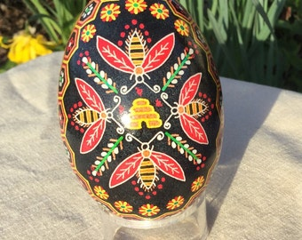 Hived honeybees and flowered honeycomb border goose pysanka with black background