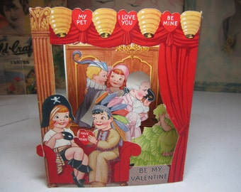Colorful large die cut shadow box style art deco 1930's valentine card shows children dressed in costume,pirate, indian,powdered wigs,etc.