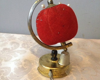 Vintage red velvet globe pincushion with built-in tape measure and thimble holder