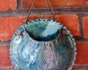 Deep, blue green, ceramic wall pocket has an embossed leaf design and can be used as a planter or hanging vase.