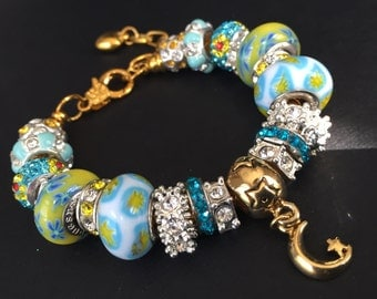Gold tone teal and yellow moon charm bracelet.