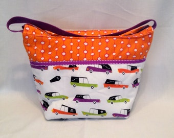 "Lunch Bag: ""Driven to Eat"" washable insulated lunch bag with zippered front pocket and zippered top closure."