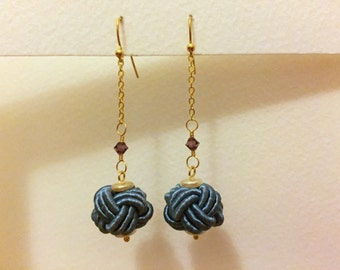 Blue Chinese knot earrings swinging from a chain and Swarovski bead