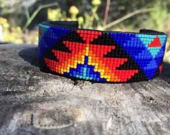 Beaded Cuff Bracelet in Light Red, Orange, Yellow and Blues on a Black Background. This Geometric Design Cuff is Handmade by the Artist.