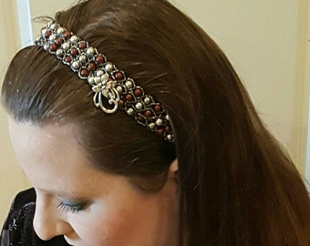 A headband made of 117 gray and Bordeaux Swarovski Crystal pearls wrapped in dark gray seed beads, with a silver flower option