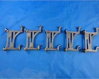 A set of 5 beautiful Arts and Crafts style cast iron Mackintosh coat hooks