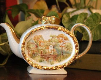 Tea Pot with Victorian Country Scene with Thatched Houses with Children Rowing a Boat in the river