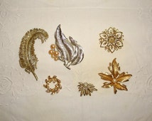Vintage costume jewelry lot of brooches. Two are marked Sarah Cov and the gold tone leaf has a real pearl in it.
