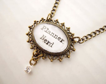 Planner Nerd necklace in an Ornate antique brass color frame Setting with crystal w distressed typewritter script