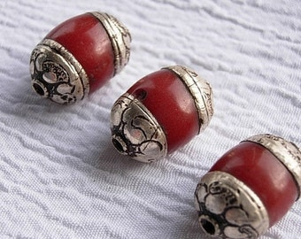 Tibetan silver repoussee capped red resin beads. Vintage red and silver antiqued beads, bead caps, jewelry making, crafts.
