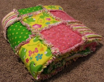 Small child-sized yellow, green, and pink frog themed rag quilt
