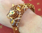 fantastic bangle bracelet topped with an amazing brown/gold tiger with gripping emerald eyes