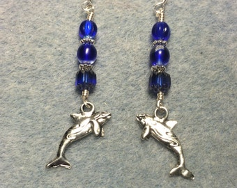 Silver whale charm dangle earrings adorned with dark blue Czech glass beads.