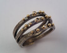 Golden water drops on a bryony tendril. A Modern gold and oxidized silver ring with diamonds and studded gold granules.