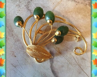 Vintage gold tone brooch with green accents