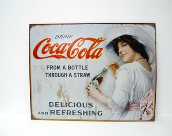 Coca-Cola from a bottle through a straw . reproduction tin sign