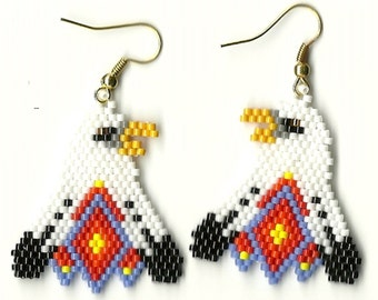 A pair of hand beaded Bald Eagle dangle earrings with a blue diamond in the feather on the bottom on the bottom