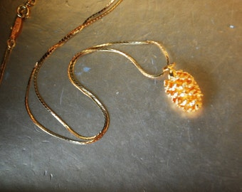 Christmas vintage 80s gold tone, shiny metal necklace with a pine cone pendant. Made by Napier.