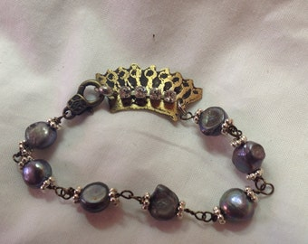 Etched metal crown and pearl bracelet